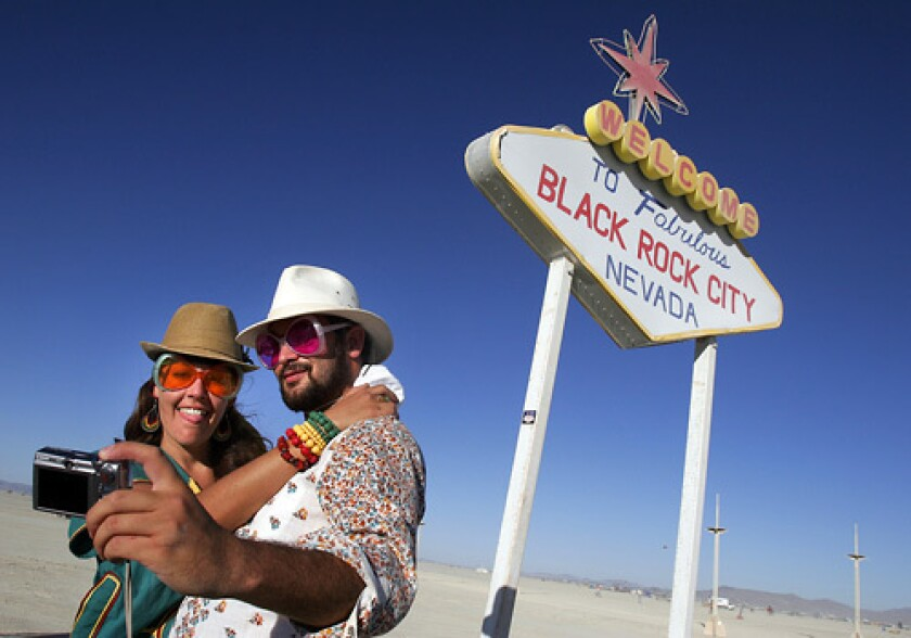 Simone Oliver of San Diego and Eric Weisz of San Francisco take a picture in front of a welcome to Black Rock City sign. Burning Man 2008 kicked into full gear as participants from around the world begin to arrive in Nevada for the annual art event that culminates with the burning of a large art installation over the weekend. More photos >>>