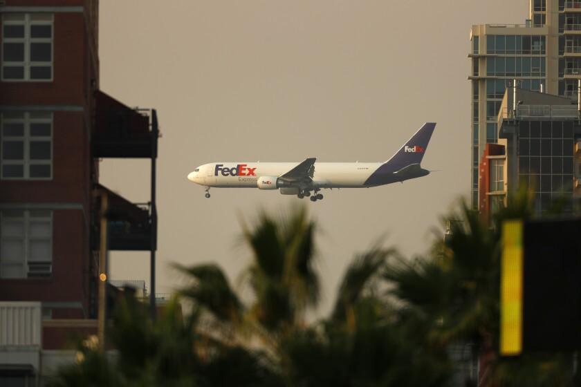 A FedEx airplane is seen between buildings before landing at the San Diego International Airport in September.