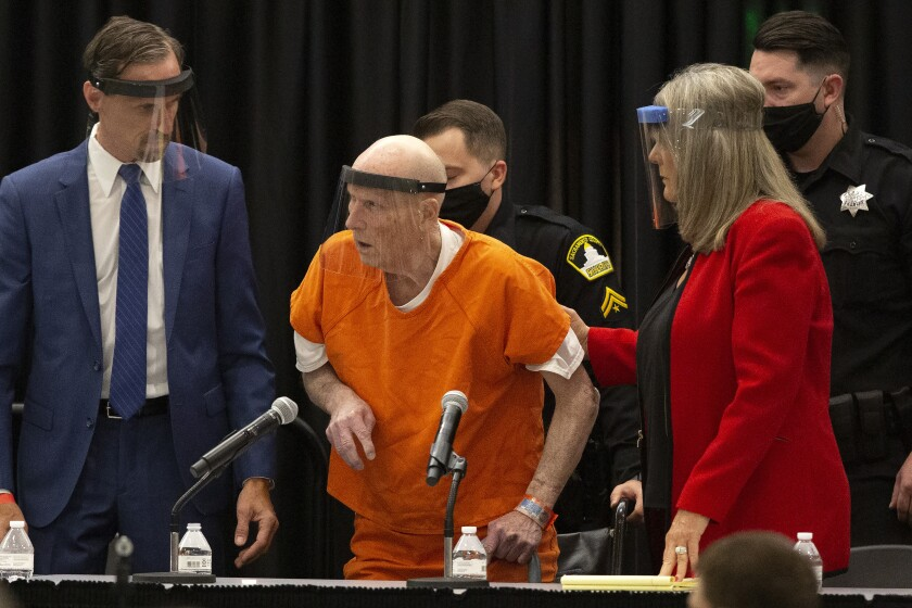 FILE - In this June 29, 2020, file photo, Joseph James DeAngelo, center, charged with being the Golden State Killer, is helped up by his attorney, Diane Howard, as Sacramento Superior Court Judge Michael Bowman enters the courtroom in Sacramento, Calif. Survivors plan to confront DeAngelo this week during an extraordinary four days of court hearings before the 74-year-old is sentenced to life in prison. (AP Photo/Rich Pedroncelli, File)