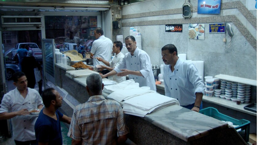 Cooks assemble koshary, classic Egyptian takeout, at Koshary Abou Tarek in downtown Cairo. Price increases of staples such as sugar, rice and wheat have made it more expensive to buy and even make koshary at home, diners say.