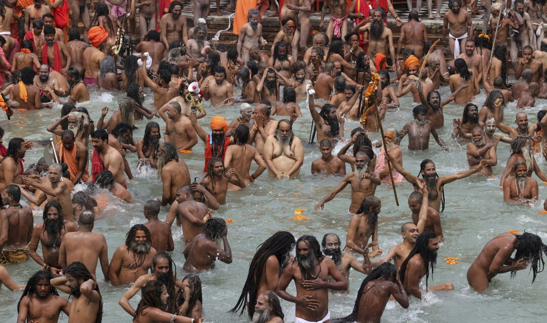 Crowds of people stand waist-deep in the Ganges River