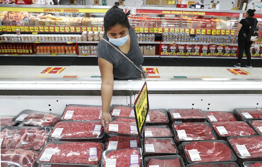 FILE - In this April 29, 2020 file photo, amid concerns of the spread of COVID-19, a shopper wears a mask as she looks over meat products at a grocery store in Dallas. The rise in wholesale prices moderated a bit in February after a record increase in January with both months being hit with higher energy prices. The Labor Department reported Friday, March 12, 2021, that its producer price index, which measures inflation before it reaches consumers. increased by 0.5% last month following a record jump of 1.3% in January. (AP Photo/LM Otero, File)