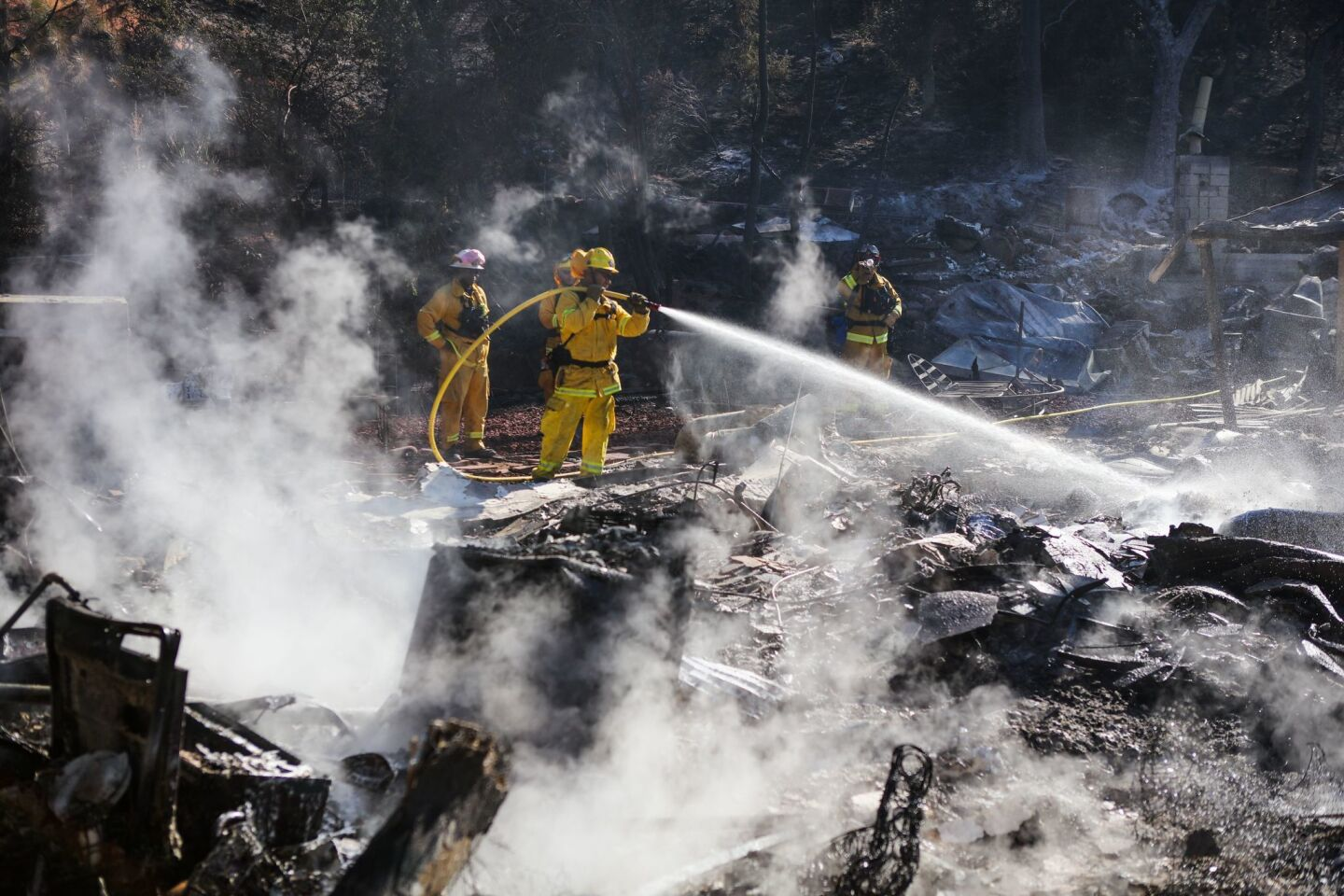 Firefighters work to contain embers on the remains of a house destroyed by the Clayton fire in Lower Lake, California.