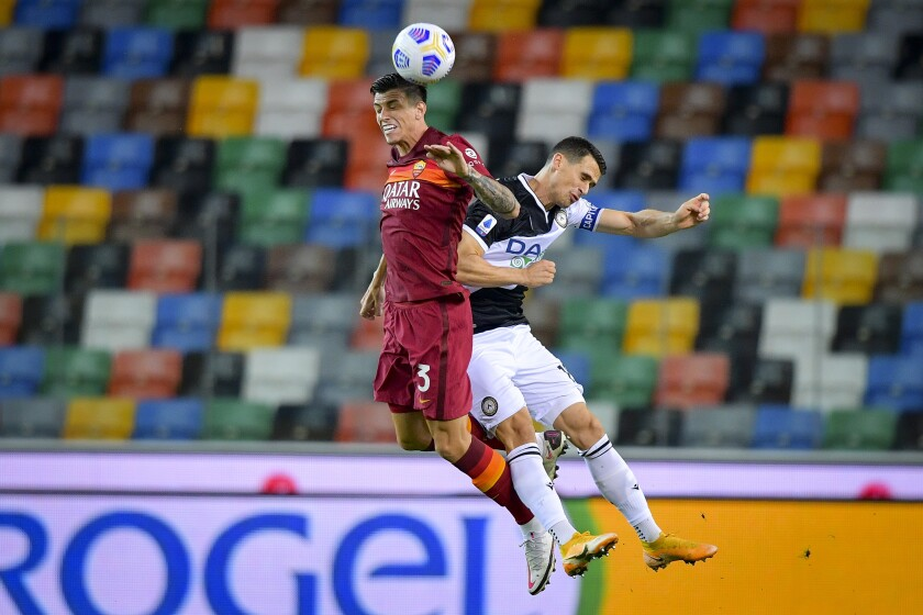 Roger Ibañez da Silva, left, and Kevin Lasagna fight for the ball during the Serie A soccer match between Udinese and Roma, at the Dacia Arena in Udine, Italy, Saturday, Oct. 3, 2020. (Fabio Rossi/LaPresse via AP)