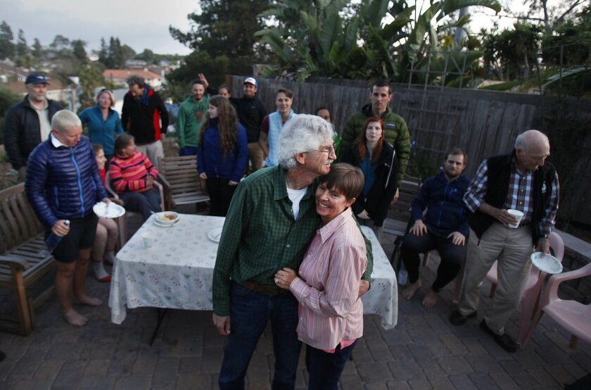 Barney Mann, left, and wife Sandy Mann shared a moment Thursday at their University City home after feeding dinner to dozens of people preparing to hike the Pacific Crest Trail.