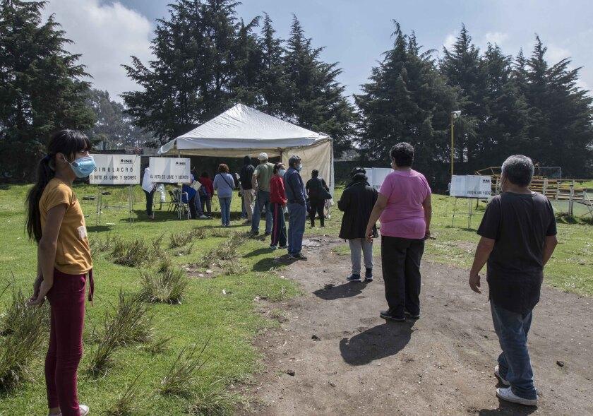 Unas personas se forman para emitir su voto en un referendo, en San Miguel Topilejo, en la Ciudad de México, el domingo 1 de agosto de 2021. (AP Foto/Christian Palma)