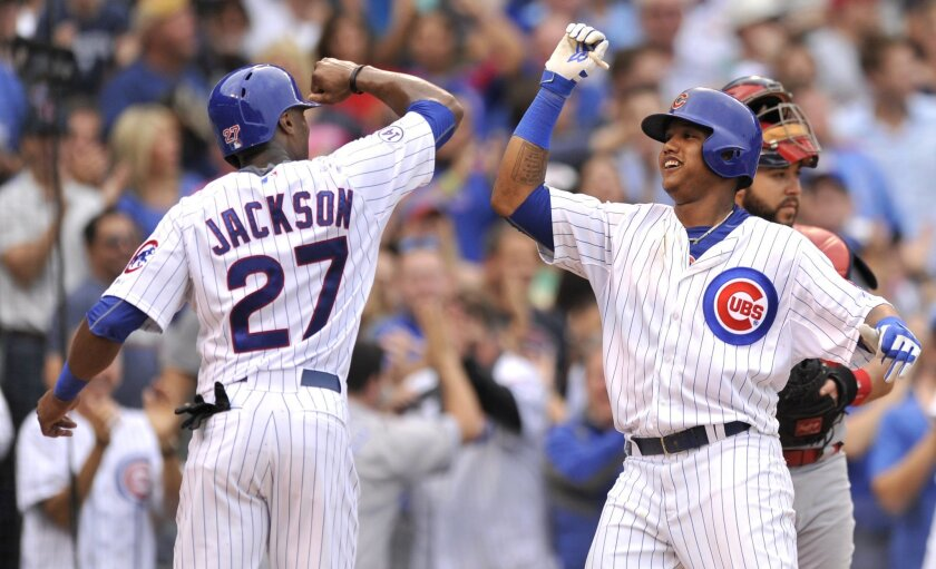 Chicago Cubs' Starlin Castro, right, celebrates with teammate Austin Jackson at home plate after hitting a three-run home run during the sixth inning of a baseball game against the St. Louis Cardinals, Friday, Sept. 18, 2015, in Chicago. (AP Photo/Paul Beaty)