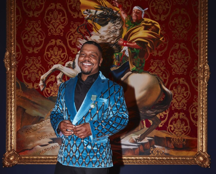 A man in a blue satin jacket stands in front of a large painting of a man on a horse