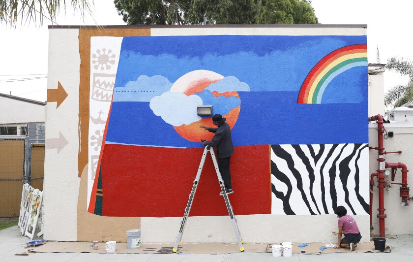 A man on a ladder paints a mural on the outside of a building, as does a woman in the bottom right corner