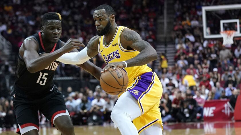 Lakers' LeBron James, right, drives toward the basket as Houston Rockets' Clint Capela (15) defends during the first half.
