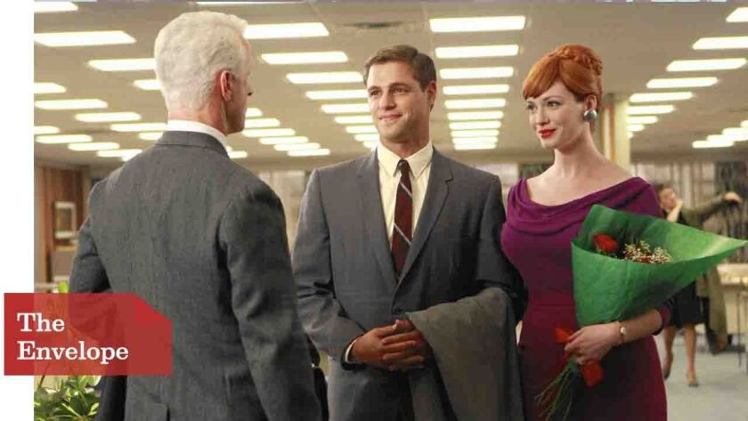 Joan (Christina Hendricks) and husband Greg (Sam Page) chat with Roger (John Slattery). Joan's rape by Greg was shocking, as was the audience response, Hendricks says.