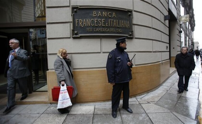In this photo taken Sept. 2, 2010, a police officer guards outside a bank in downtown Buenos Aires, Argentina. Argentines reluctance to use the banking system makes them attractive targets for attackers because they prefer to carry cash, even for large operations, such as buying cars or properties. (AP Photo/Natacha Pisarenko)