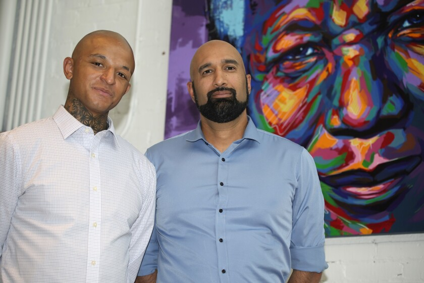 Kyle Vinson, left, stands with his attorney, Qusair Mohamedbhai, on Wednesday, Aug. 4, 2021, in Denver. Aurora Officer John Haubert was arrested Monday on suspicion of attempted first-degree assault, second-degree assault and felony menacing charges following a criminal investigation into the arrest last week of Vinson, who is biracial and identifies as Black. (AP Photo/David Zalubowski)