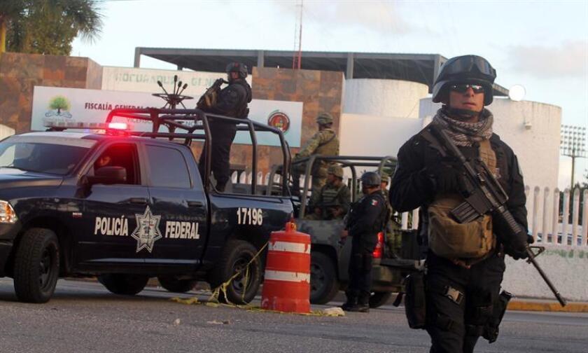 Agentes federales resguardan la Fiscalía General del estado mexicano de Quintana Roo en Cancún (México) hoy, viernes 20 de enero de 2017, por la amenaza de un nuevo atentado luego de que el pasado martes se produjo un ataque a esta dependencia que dejó cuatro muertos. La zona donde se encuentra el edificio de la Fiscalía fue nuevamente acordonada por elementos de la Gendarmería Nacional y el Ejército Mexicano, aunque finalmente se determinó la falsedad de la amenaza, la mayoría de los empleados ya no regresaron a las instalaciones, pues ya casi era la hora de salida. EFE
