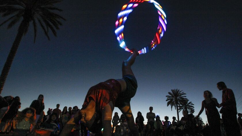 Twirling a hula hoop with lights, a fireworks spectator gives an impromtu show just before the fireworks display during a City of Oceanside Fourth of July celebration.