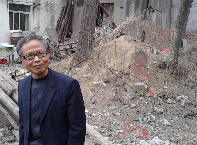 Zhang Hongbing stands at the site of his mother's grave, marked by a red stone visible in the background, in Guzhen, China. She was executed in the Cultural Revolution in 1970. Zhang wants to put up a memorial.