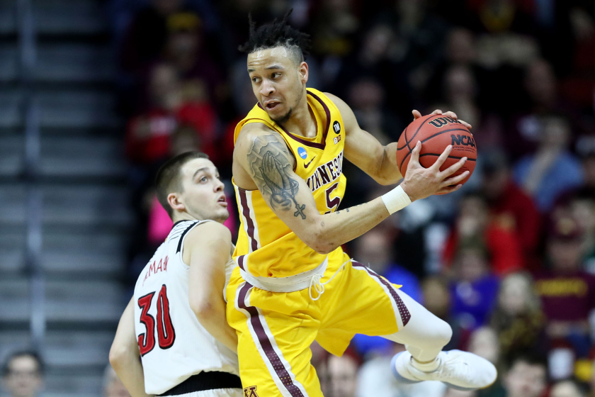 Amir Coffey of the Minnesota Golden Gophers controls the ball against Louisville.