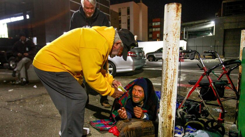 San Diego Veterans for Peace volunteer Stan Levin, 88, gives Shayne Dunn, who is homeless, a package of food before he and Gilbert Fields, background, a new sleeping bag in downtown San Diego on Friday.