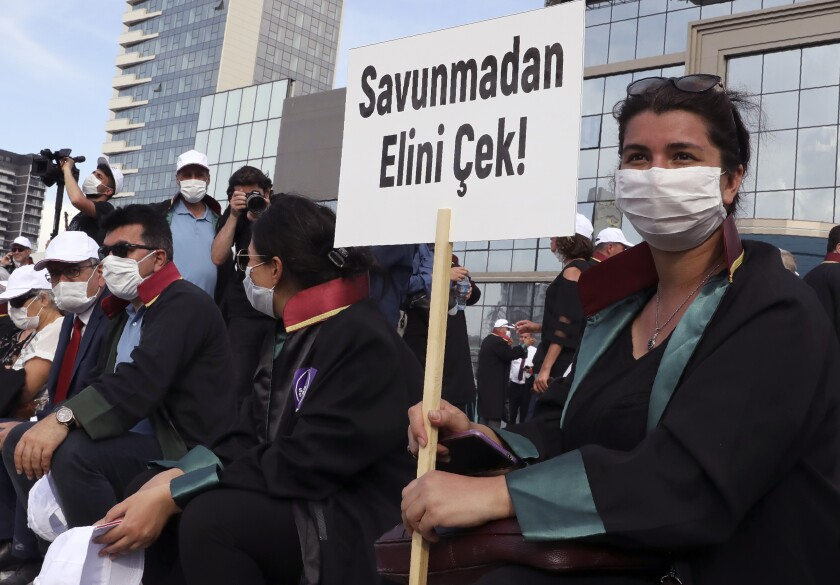 "Lawyers wearing face masks to protect against the spread of coronavirus, as one holds a placard that reads ""Don't touch the Defence!"" during a protest, in Ankara, Turkey, Monday, June 22, 2020. Turkish authorities have made the wearing of masks mandatory in three major cities to curb the spread of COVID-19 following an uptick in confirmed cases since the reopening of many businesses. (AP Photo/Burhan Ozbilici)"