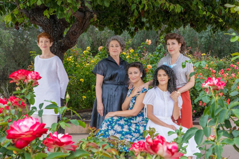 """""""The Gardens of Anuncia"""" cast is photographed in a garden filled with rose plants"""