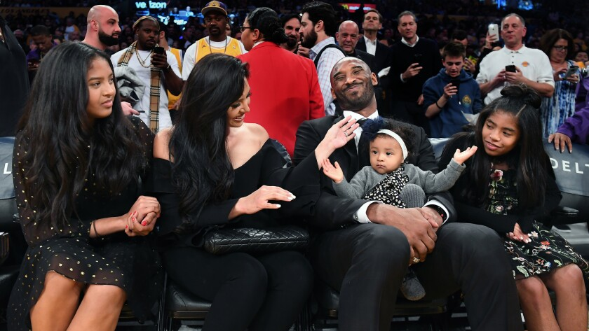 Former Laker Kobe Bryant sits courtside with his family before a jersey retirement ceremony on Dec. 18, 2017.