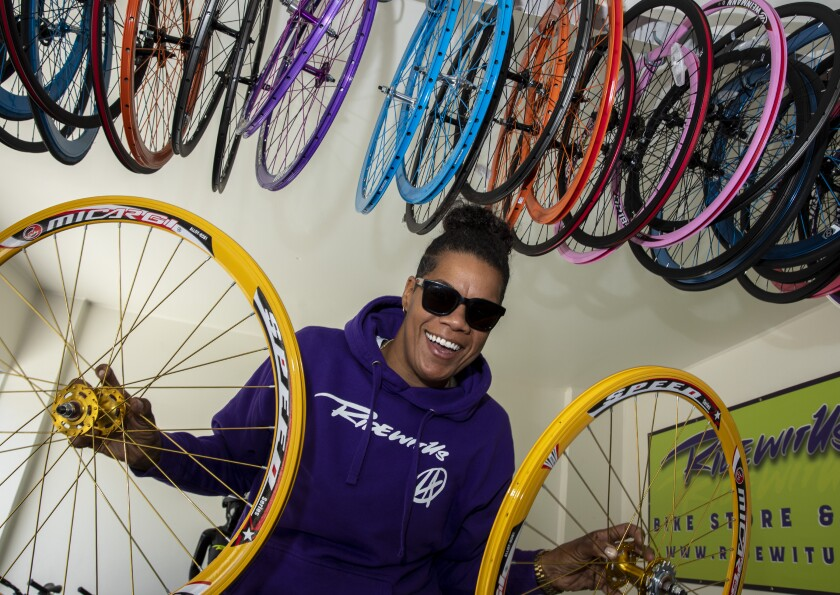 A woman smiles while holding two yellow bike wheels in front of a wall of multicolored wheels