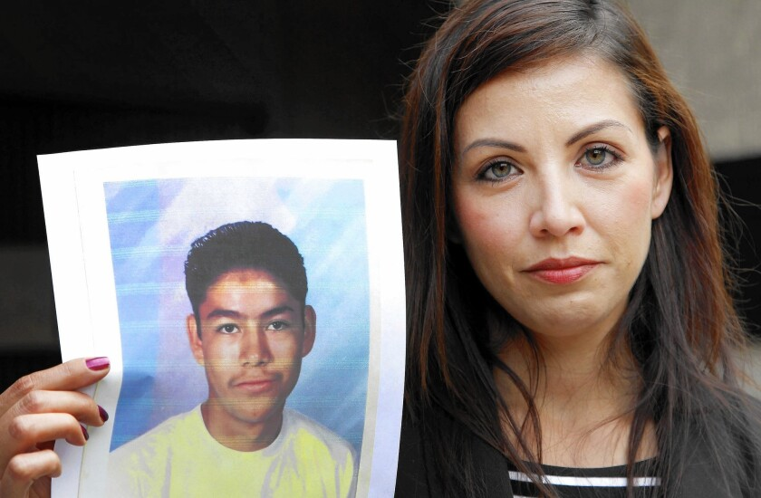 Lydia Espinoza Oregel, at a 2013 news conference, shows a photo of her brother Edel Gonzalez when he was 16.