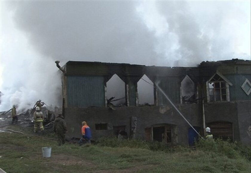 In this photo released by the Novgorod region branch of Russian Emergency Ministry, the ministry's Emergency Situations workers and fire fighters work at a site of a fire at a psychiatric hospital in Luka village in the Novgorod region, Russia, early Friday, Sept. 13, 2013. A fire swept through the Russian psychiatric hospital overnight, killing at least three people and leaving more than 30 others feared dead, officials said Friday. Authorities had long warned that the building was unsafe and c