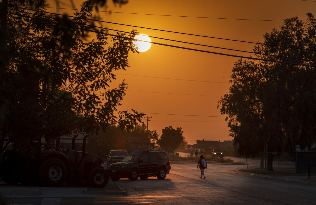A high schooler walks towards a bus stop as the sun rises above Main Street in Stratford.