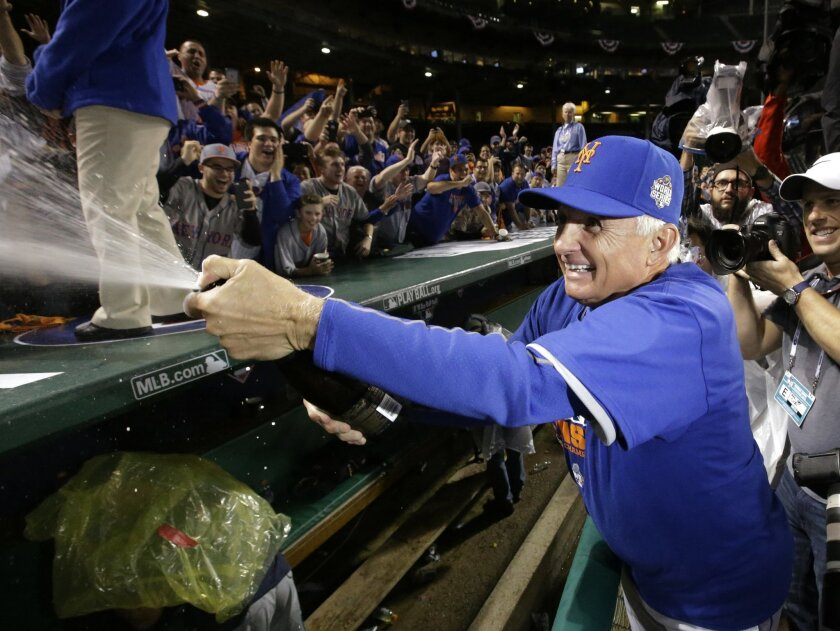 New York Mets manager Terry Collins sprays the crowd after Game 4 of the National League baseball championship series against the Chicago Cubs Wednesday, Oct. 21, 2015, in Chicago. The Mets won 8-3 to advance to the World Series. (AP Photo/Nam Y. Huh)