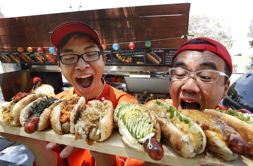 Hideki Aizawa, left, marketing manager, and Noriki Tamura, owner of Japadog, display the different hot dogs they make.