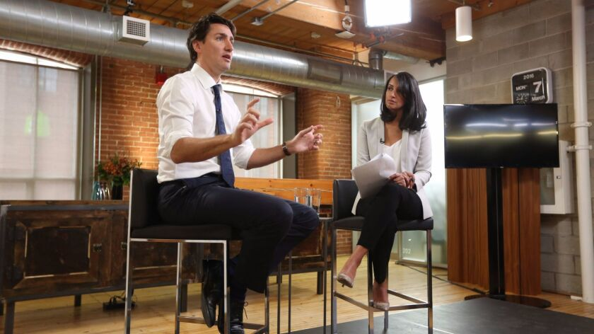 Canada's Prime Minister Justin Trudeau, left, speaks at a global town hall hosted by The Huffington