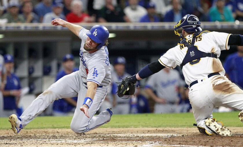 Dodgers shortstop Charlie Culberson dives around the tag attempt of Padres catcher Derek Norris to score a run in the sixth inning.