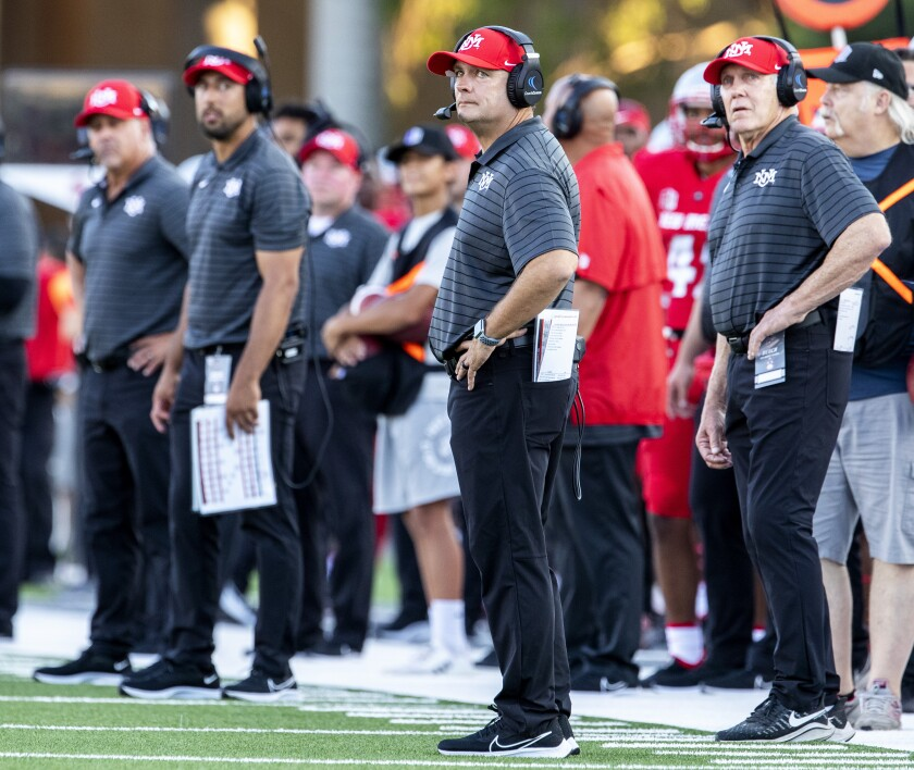 New Mexico head coach Danny Gonzales, center, and defensive coordinator Rocky Long, right.