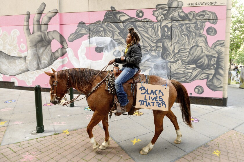 Brianna Noble rides her horse, Dapper Dan, through downtown Oakland on May 29.