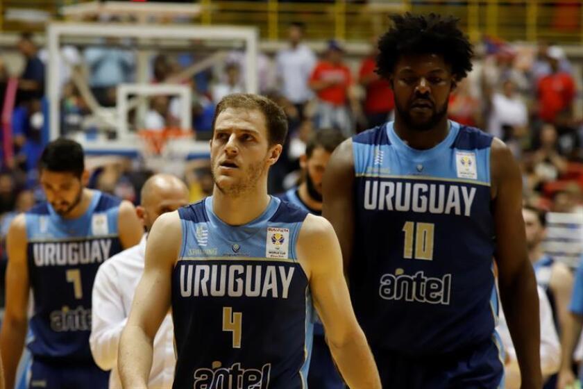 Los uruguayos Santiago Vidale (c) y Hatila Passos (d) salen de la cancha este lunes, en el último juego de la clasificación al Campeonato Mundial de Baloncesto China 2019 entre Puerto Rico y Uruguay, en el Coliseo Roberto Clemente en San Juan (Puerto Rico). EFE