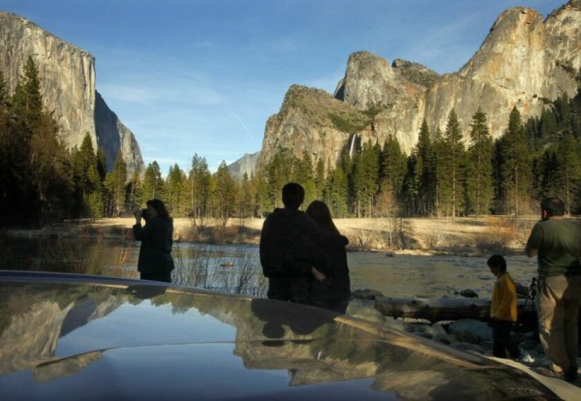 Visitors to the park stop to look, photograph and enjoy the light and scenery of the Yosemite Valley on a cool spring evening.