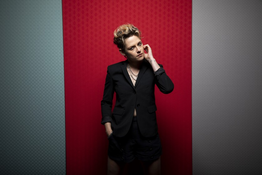 Kristen Stewart poses with her hand on her cheek at the Toronto Film Festival in front of a red and gray backdrop