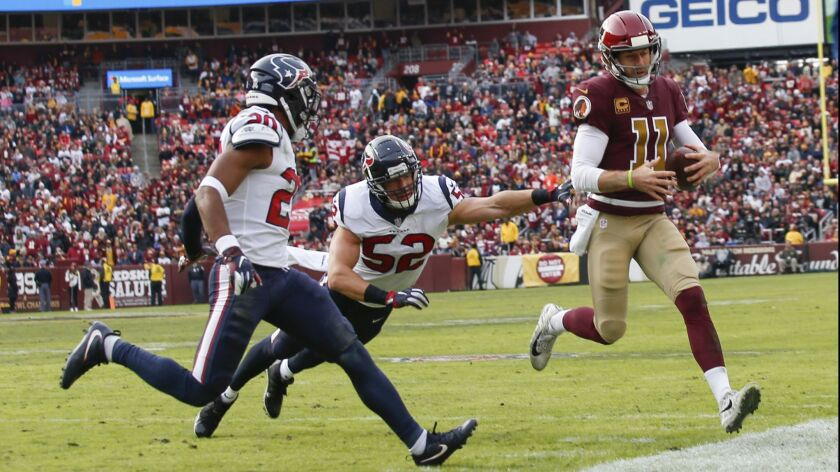 Redskins quarterback Alex Smith scrambles during the first half of Sunday's game against the Texans.