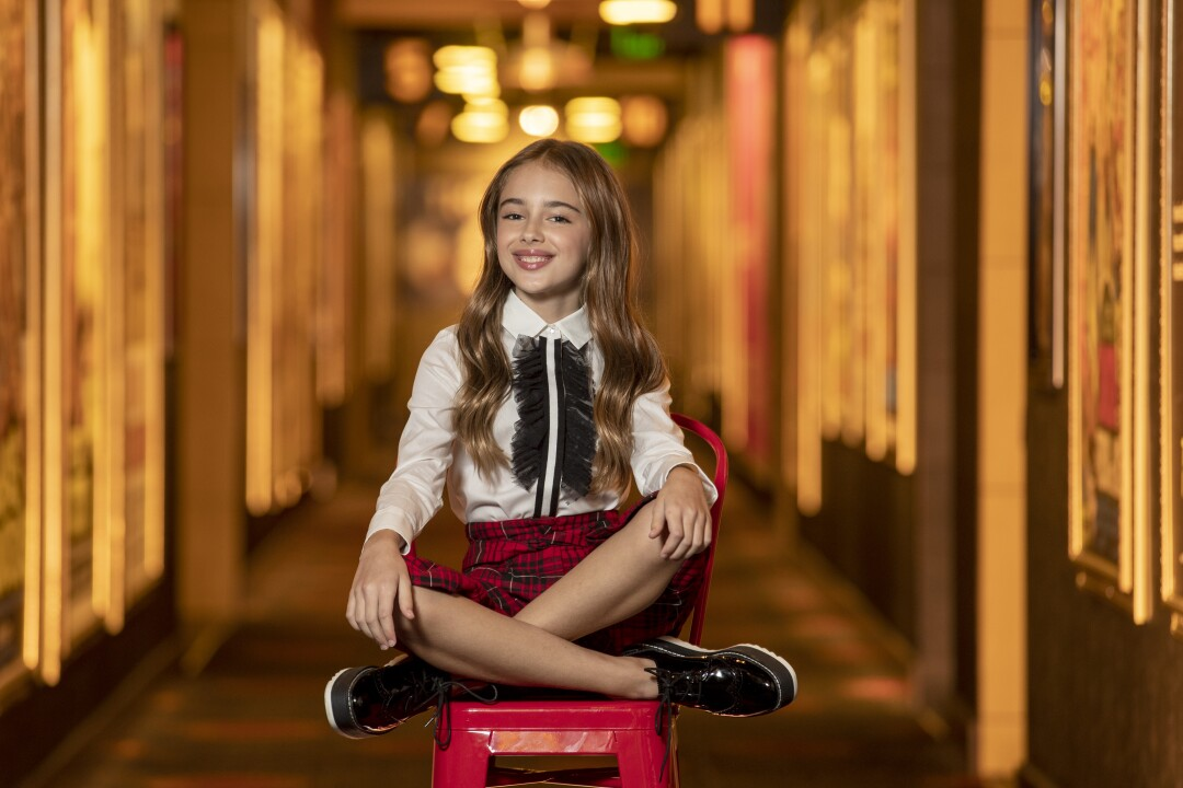 Julia Butters, 10, sitting cross-legged on a red chair.