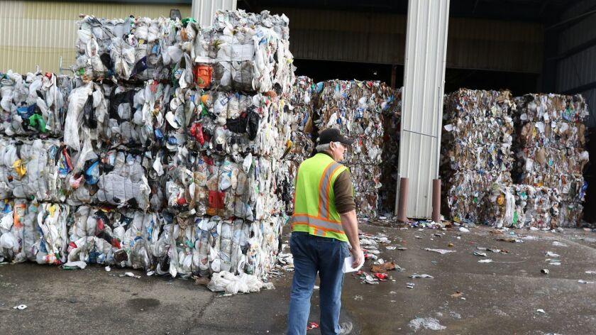Sunrise Enterprises recycle manager Steven Buckley walks toward bundled materials waiting to be tran