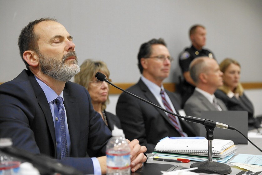 Charles Lester, left, reacts as he hears the vote to fire him as executive director of the California Coastal Commission.