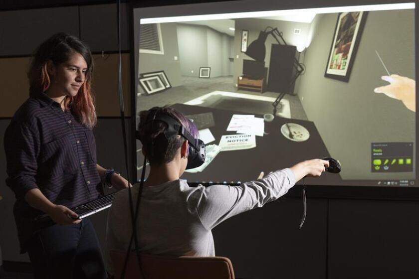 Fotografía cedida por el Laboratorio de Interacción Humana Virtual de la Universidad de Stanford donde aparece Fernanda Herrera (i) mientras observa a Hannah Mieczkowski (d) navegando a través de una experiencia virtual que comienza con una notificación de desalojo. EFE/Linda A. Cicero/Stanford News/SOLO USO EDITORIAL/NO VENTAS