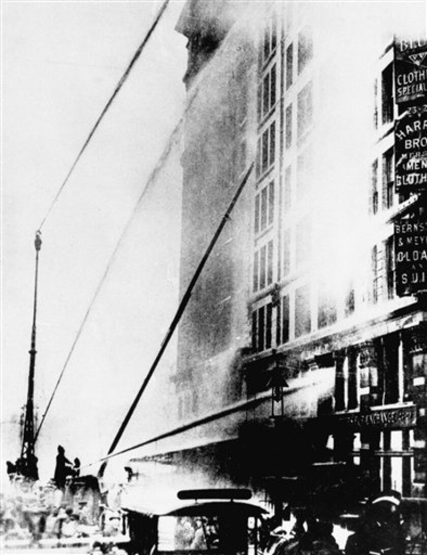 FILE - In this March 25, 1911 file photo, firefighters work to put out the fire at the Triangle Shirtwaist Company in New York's Greenwich Village neighborhood. One hundred years ago, horrified onlookers watched as workers leapt to their deaths from the raging fire in the garment factory. The fire killed 146 workers, mainly young immigrant women and girls, and became a touchstone for the organized labor movement, spurred fire-safety laws and shed light on the lives of immigrant workers. (AP Photo/File)