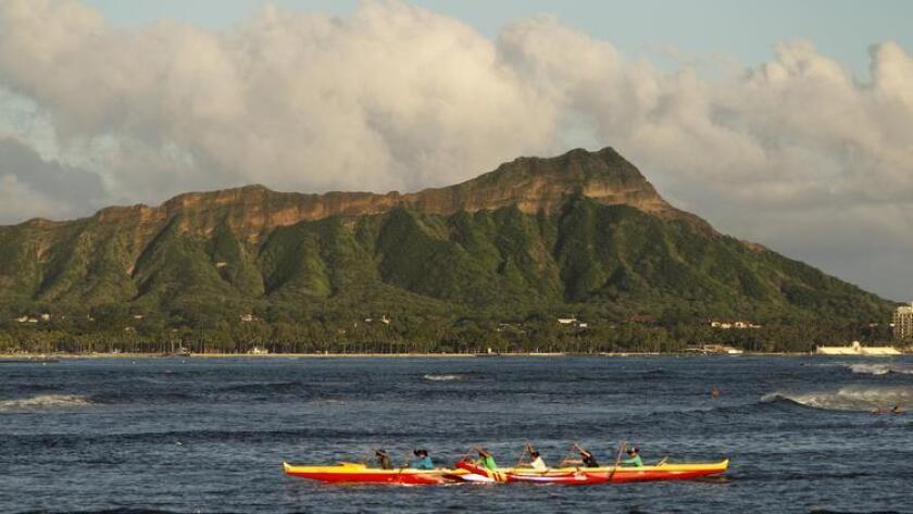 Una canoa con portaremos exteriores pasando más allá de la montaña de Diamond Head en Honolulu. Hawái es un destino popular para los legisladores de California cada mes de noviembre, aunque prefieren Maui.