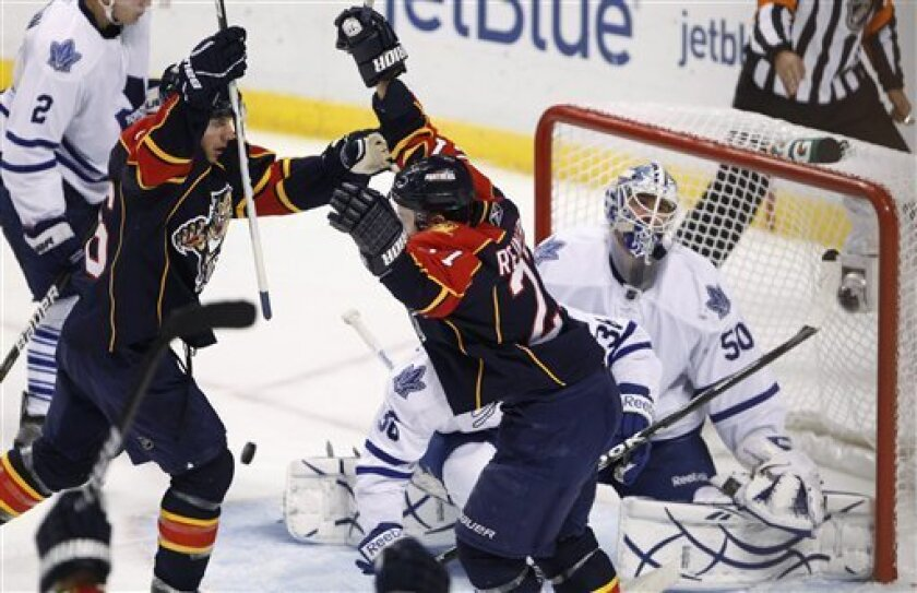 Florida Panthers center Steve Reinprecht, center, and right wing Steve Bernier, left, celebrate after Reinprecht scored against Toronto Maple Leafs goalie Jonas Gustavsson, rear, during the second period of an NHL hockey game Wednesday, Nov. 10, 2010, in Sunrise, Fla. (AP Photo/Wilfredo Lee)
