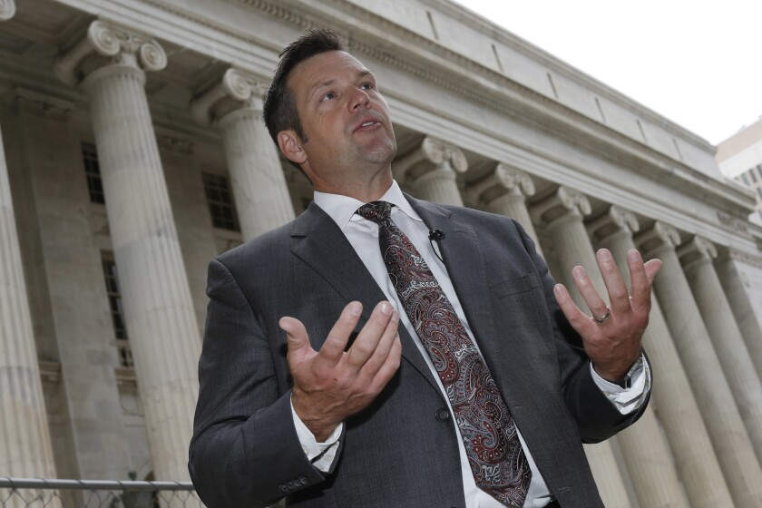 Kansas Secretary of State Kris Kobach responds to questions outside the 10th U.S. Circuit Court of Appeals in August.