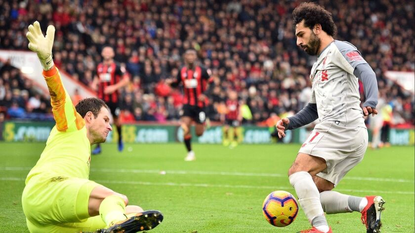 Liverpool's midfielder Mohamed Salah (R) dribbles the ball around Bournemouth's goalkeeper Asmir Begovic in the build-up to scoring his third goal in the game.
