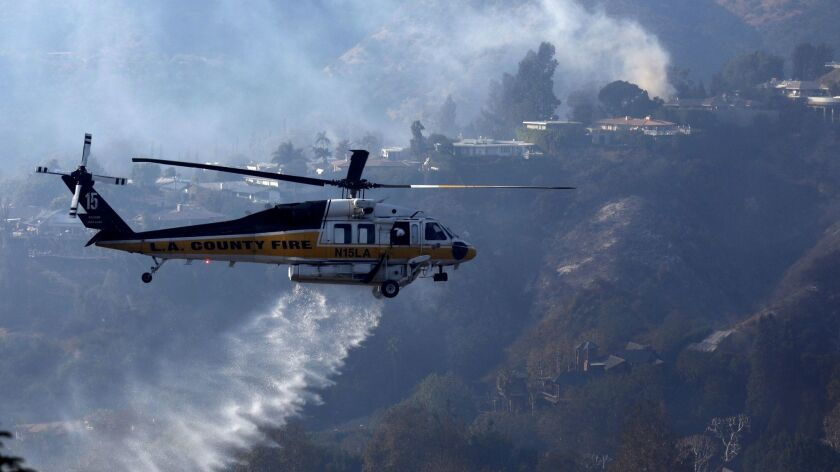 A helicopter does a water drop against a row of homes that are still threatened by the Skirball fire