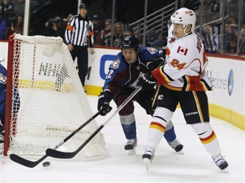 Calgary Flames center Jiri Hudler, right, of the Czech Republic, vies for control of the puck with Colorado Avalanche defenseman Matt Hunwick during the second period of an NHL hockey game in Denver on Thursday, Feb. 28, 2013. (AP Photo/David Zalubowski)